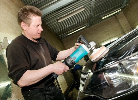 polisher: car care work with machine polisher at service station