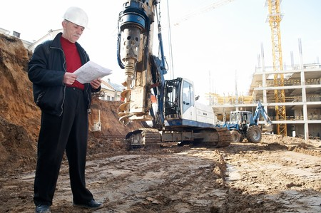 works: builder inspector worker at construction site with documentation