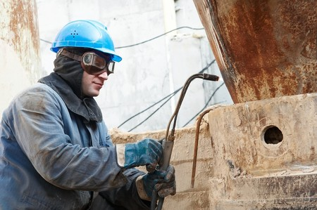 manual worker in protective work wear  welding by gas torch photo