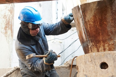manual worker in protective work wear  beating a metal form by hammer photo
