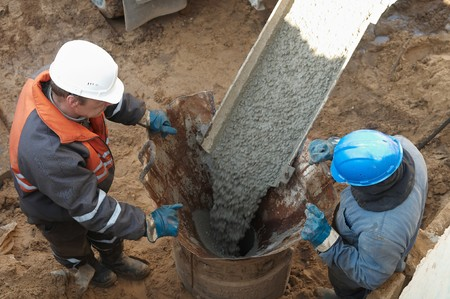 concrete form: couple workers making pile form filling with continuous concrete casting