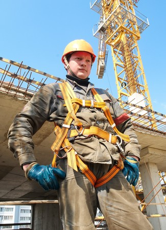 Young builder worker in work wear, helmet and equipment at house building area Stock Photo - 7398163