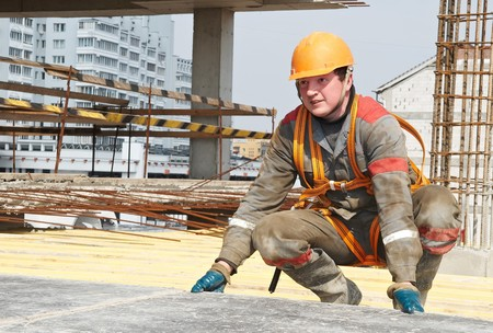 erector: Young builder worker in work wear, helmet and equipment at house building area Stock Photo