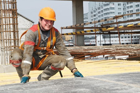 millwright: Young builder worker in work wear, helmet and equipment at house building area Stock Photo