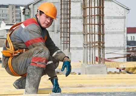 taskmaster: Young builder worker in work wear, helmet and equipment at house building area Stock Photo