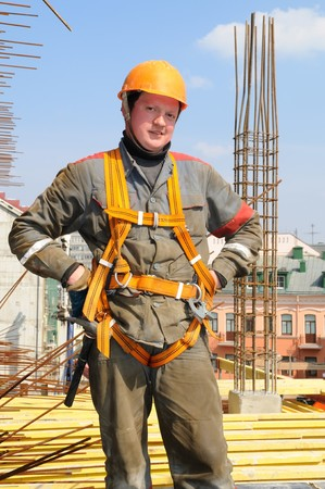 mounter: Young builder worker in work wear, helmet and equipment at house building area Stock Photo