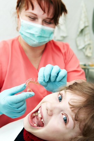 dentistry: orthodontic doctor examine teeth and gums of little girl jaw