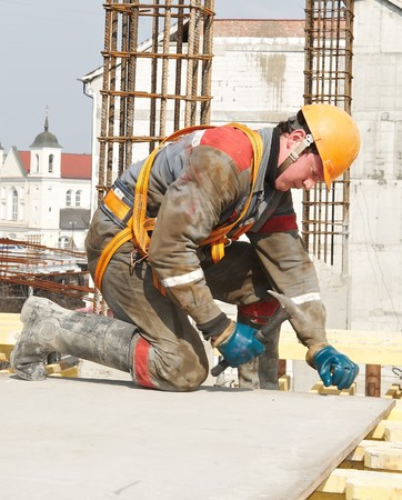 mounter: builder working in protective wear, helmet and equipment  Stock Photo