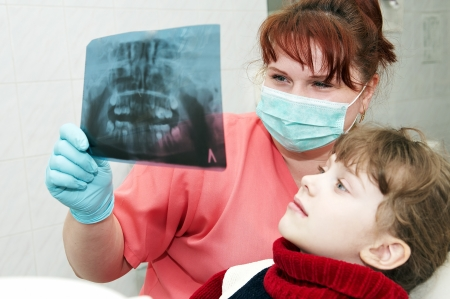 orthodontic doctor examine with little girl x-ray image of teeth and gums photo