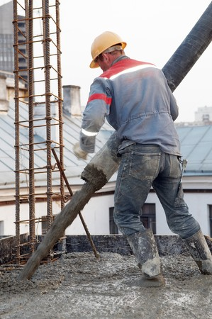 foremaster: builder worker aiming pump tube during concrete pouring process