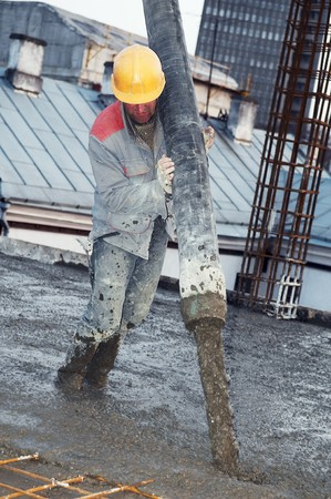 builder worker aiming pump tube during concrete pouring process photo
