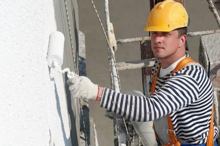 pintora: fachada de pintura de trabajador de generador de rascacielos edificio con rodillos  Foto de archivo