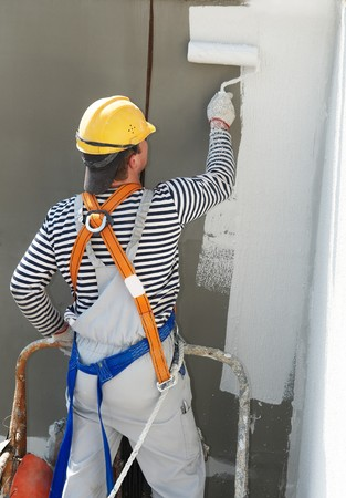 builder worker painting facade of high-rise building with roller photo