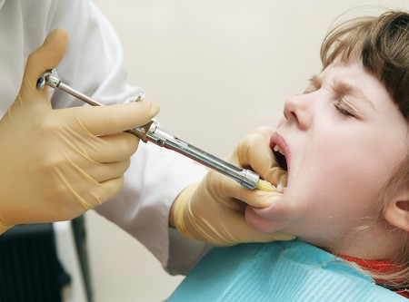 anaesthetic: Dentist making anesthetic injection to child gum before milk tooth extracting Stock Photo