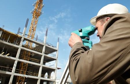 encuestando: trabajador agrimensor medir distancias, altitudes y direcciones en sitio de construcción por equipos de tránsito nivel teodolito  Foto de archivo