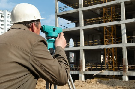 elevation meter: worker surveyor measuring distances, elevations and directions on construction site by theodolite level transit equipment Stock Photo