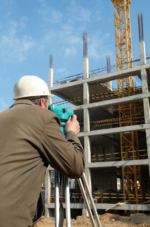 worker surveyor measuring distances, elevations and directions on construction site by theodolite level transit equipment Stock Photo - 7421542