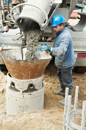 poling: construction worker controlling pile form filling with continuous concrete casting