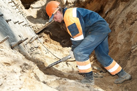 pressured: young builder at construction site working with pneumatic plugger hammer Stock Photo
