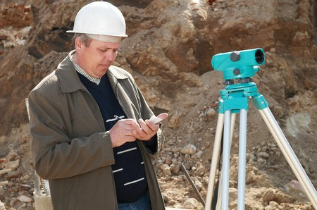 worker surveyor measuring distances, elevations and directions on construction site by theodolite level transit equipment Stock Photo - 7397881