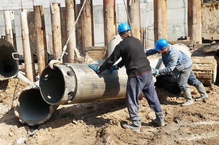 piling: couple workers installing a tube metal form for piling with continuous concrete casting Stock Photo