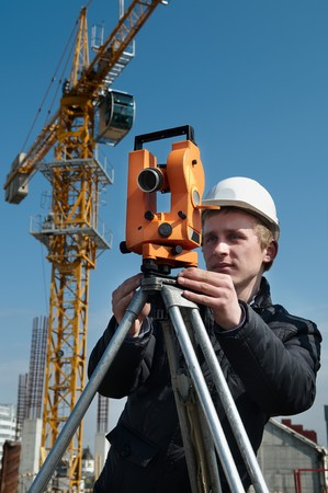 worker surveyor measuring distances, elevations and directions on construction site by theodolite level transit equipment photo