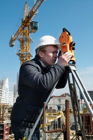 geodesist: worker surveyor measuring distances, elevations and directions on construction site by theodolite level transit equipment Stock Photo