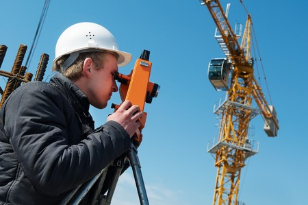 worker surveyor measuring distances, elevations and directions on construction site by theodolite level transit equipment Stock Photo - 7397882