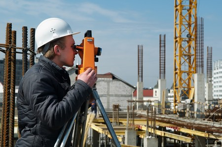 theodolite: worker surveyor measuring distances, elevations and directions on construction site by theodolite level transit equipment Stock Photo