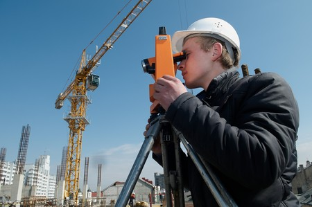 worker surveyor measuring distances, elevations and directions on construction site by theodolite level transit equipment Stock Photo - 7421536