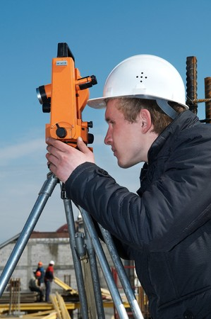topographical: worker surveyor measuring distances, elevations and directions on construction site by theodolite level transit equipment Stock Photo