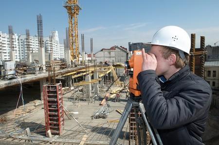 teodolito: trabajador agrimensor medir distancias, altitudes y direcciones en sitio de construcción por equipos de tránsito nivel teodolito  Foto de archivo
