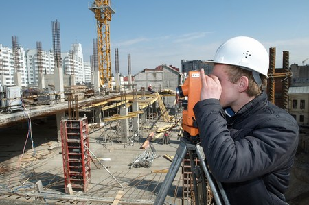 land surveyor: worker surveyor measuring distances, elevations and directions on construction site by theodolite level transit equipment Stock Photo