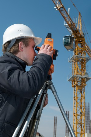 worker surveyor measuring distances, elevations and directions on construction site by theodolite level transit equipment Stock Photo - 7397877