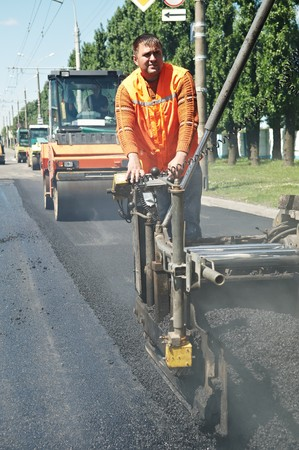 asphalting: Young builder on Asphalting paver machine during Road street repairing works Stock Photo