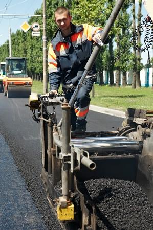 asphalting: Young builder on Asphalting paver machine during Road street repairing works Stock Photo