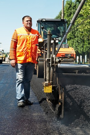 Young builder on Asphalting paver machine during Road street repairing works photo