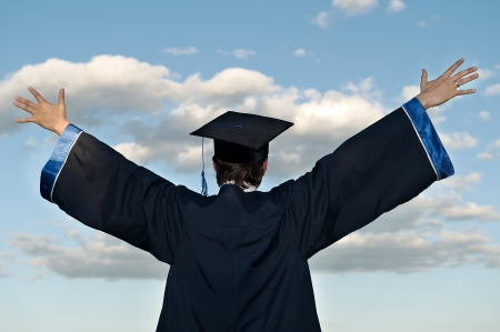 graduation gown: graduate student in cloak with open arms over blue sky (rear view) Stock Photo