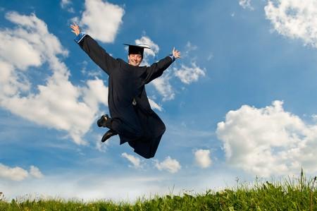 toga y birrete: Smiley joven estudiante graduado en Bata saltando de cielo azul
