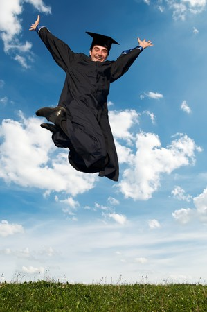 Young smiley graduate student in gown jumping over blue sky photo