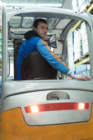 Worker driver of a forklift loader at food warehouse distribution works photo