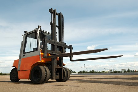 Forklift loader for warehouse works outdoors with risen forks photo