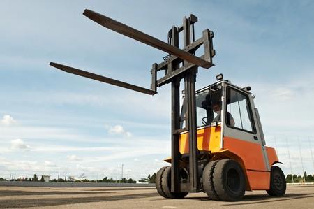 Forklift loader for warehouse works outdoors with risen forks photo