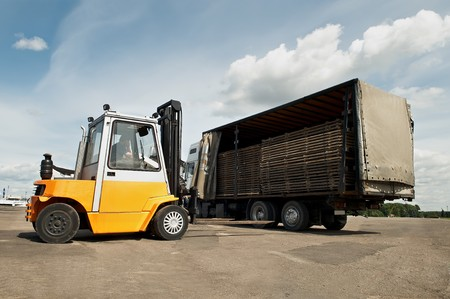 handling: Forklift loader for warehouse works outdoors loading (unloading) a long lorry truck