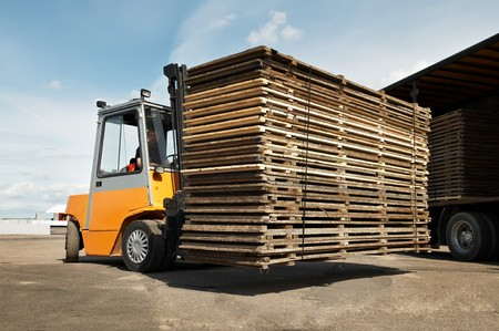 Forklift loader for warehouse works outdoors loading (unloading) a long lorry truck photo