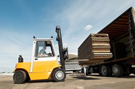 forklift truck: Forklift loader for warehouse works outdoors loading (unloading) a long lorry truck