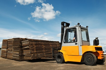 Forklift loader making warehouse works outdoors by stacking wood pallet photo
