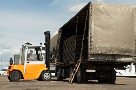 Forklift loader for warehouse works outdoors loading (unloading) a long lorry truck Stock Photo - 7399959