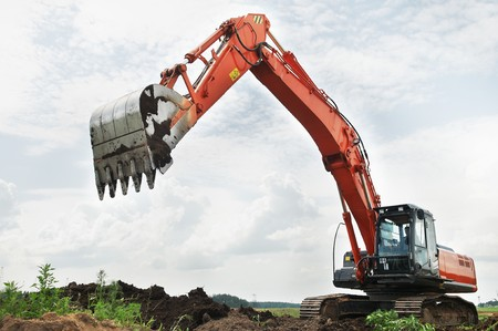 Loader Excavator doing construction works standing in field with risen bucket outdoors photo