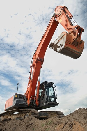 excavation: Loader Excavator doing construction works standing in field with risen bucket outdoors Stock Photo